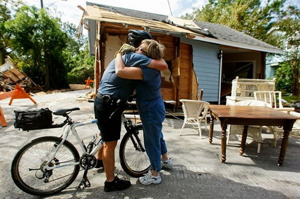Seabrook, TX police officer Jeff Galyean hugs his 4th grade teacher, Sue Harral, on Tuesday in front of her home.  The house was swept into the middle of the street and was several hundred feet from its foundation.  Mark Wilson / Getty Images