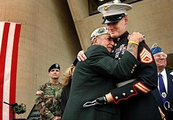 Dallas City Hall, Veterans Day, November 11, 2004. Houston James, a survivor of the attack on Pearl Harbor, hugs Marine Staff Sergeant Mark Graunke Jr., a member of an explosive disposal team who lost his left hand, one leg and an eye in Iraq.